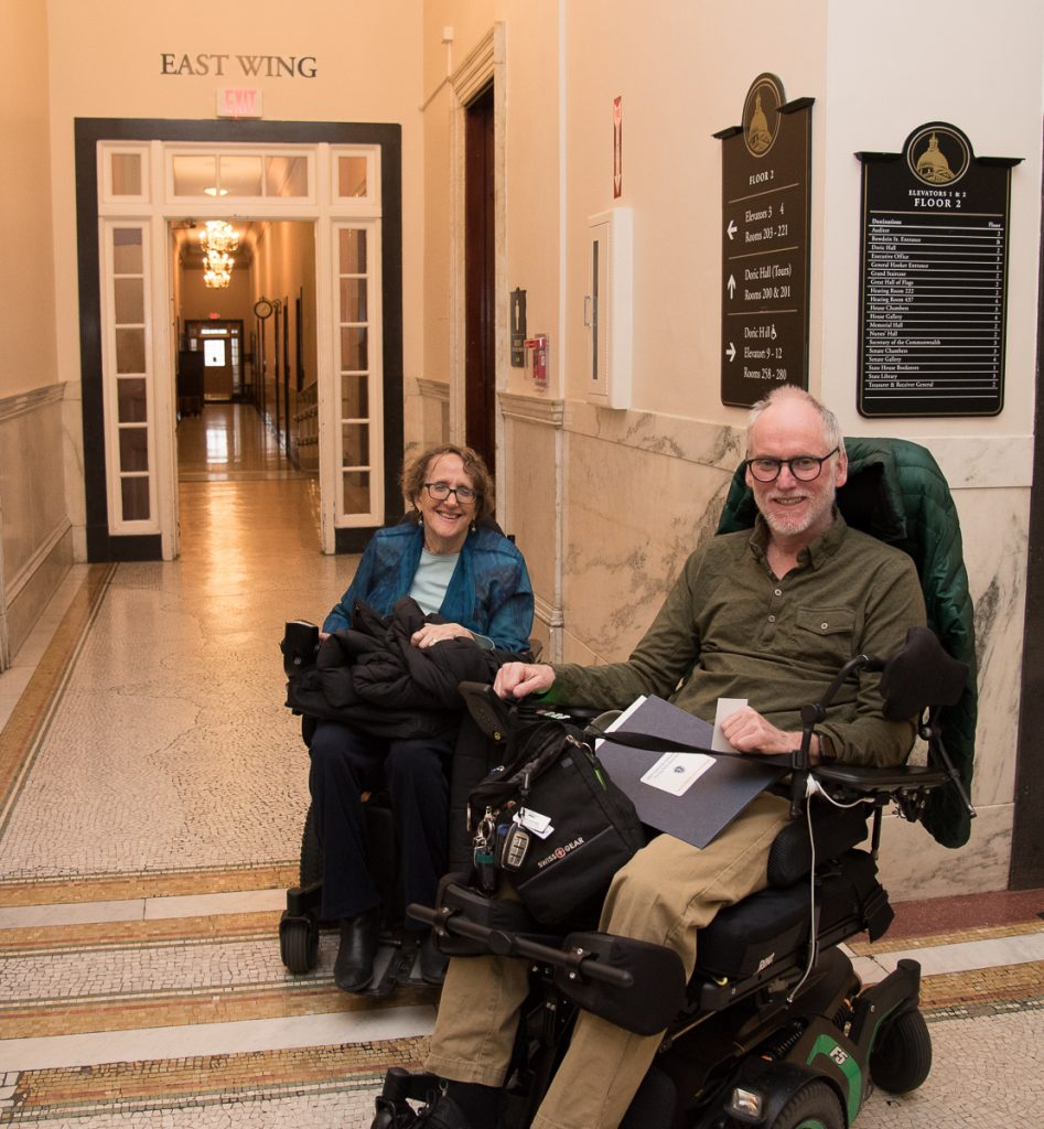 2 advocates in wheelchairs in state house hallway 2019